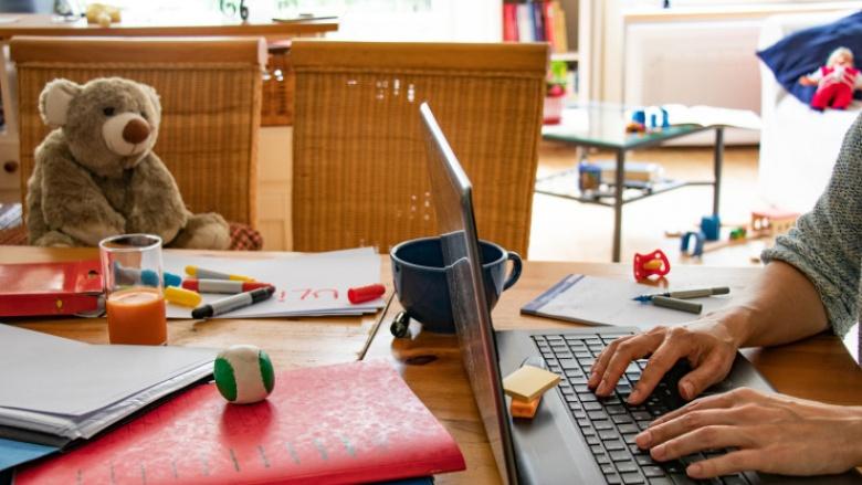 Das Bukd zeigt einen Homeoffice-Esstisch mit Laptop und Teddybär
