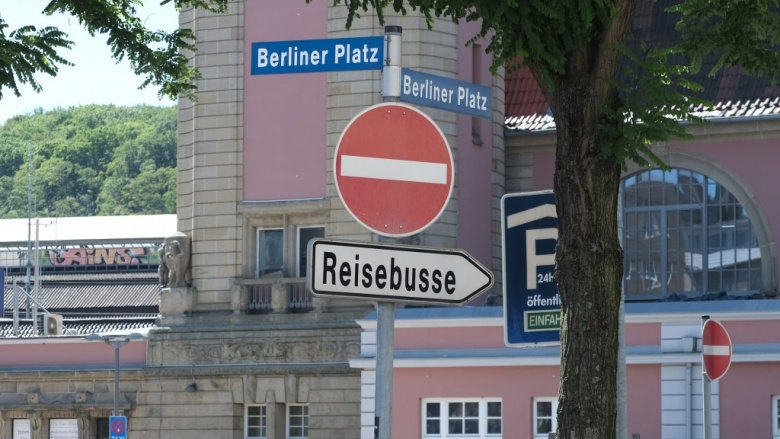 Das Bild zeigt das Hinweisschild für Reisebusse am Hagener Hauptbahnhof. Im Hintergrund: der Hauptbahnhof.