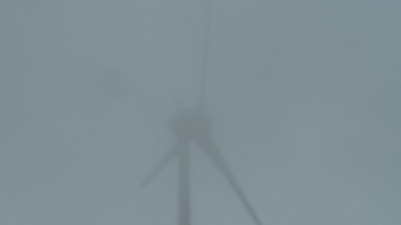 Das Bild zeigt ein Windrad im Nebel.