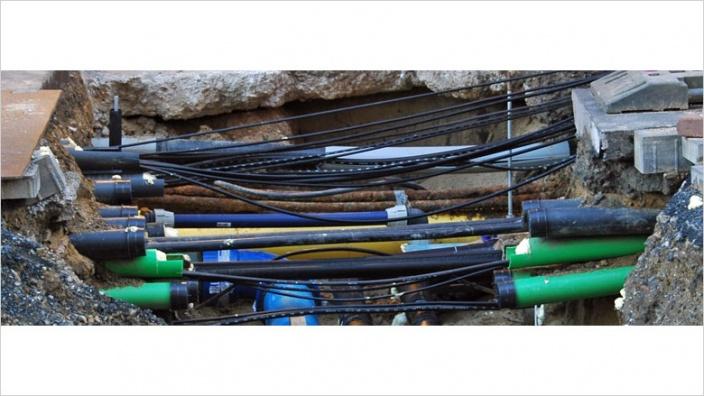Das Bild zeigt Kommunikationsleitungen in einer Baugrube.