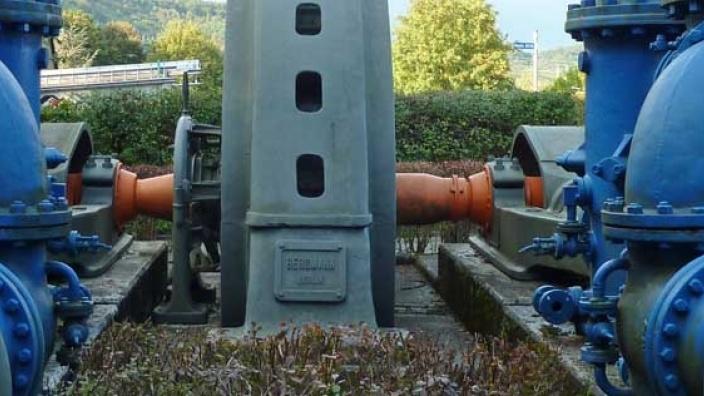 Das Bild zeigt eine alte Wasserpumpe.